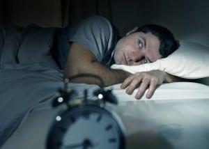 Mand ligger søvnløs i sin seng med vækkeur foran sig