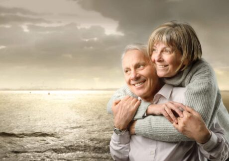 ldre ægtepar holder om hinanden med havet som baggrund