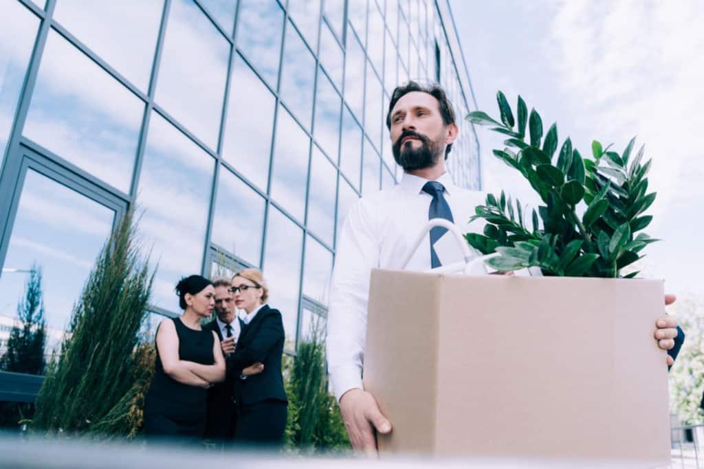 Mand med papakasse på vej ud af kontorbygning