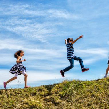 tre børn løber lystigt op af en græsklædt bakke