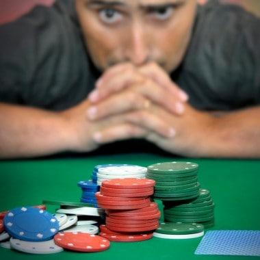 mand foran jetoner på spillebord