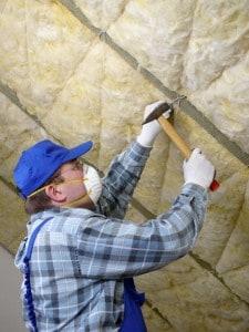 Håndværker med beskyttelsesmaske sætter isoleringsmateriale af rockwool op